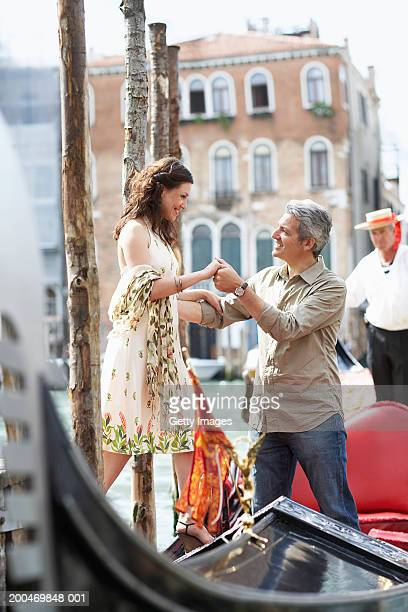Italy, Venice, man helping woman board gondola, smiling