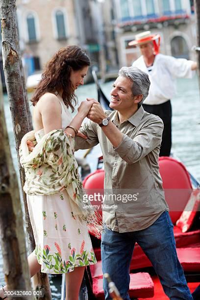 Italie, Venise, homme aidant femme monter en gondole