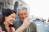 Italy, Venice, mature couple using camera, smiling (focus on couple)