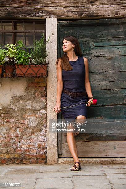 Italy, Venice, Mature woman holding red rose and standing against door