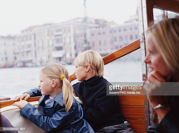 Italy, Venice, mother and children (7-10) on motorboat taxi