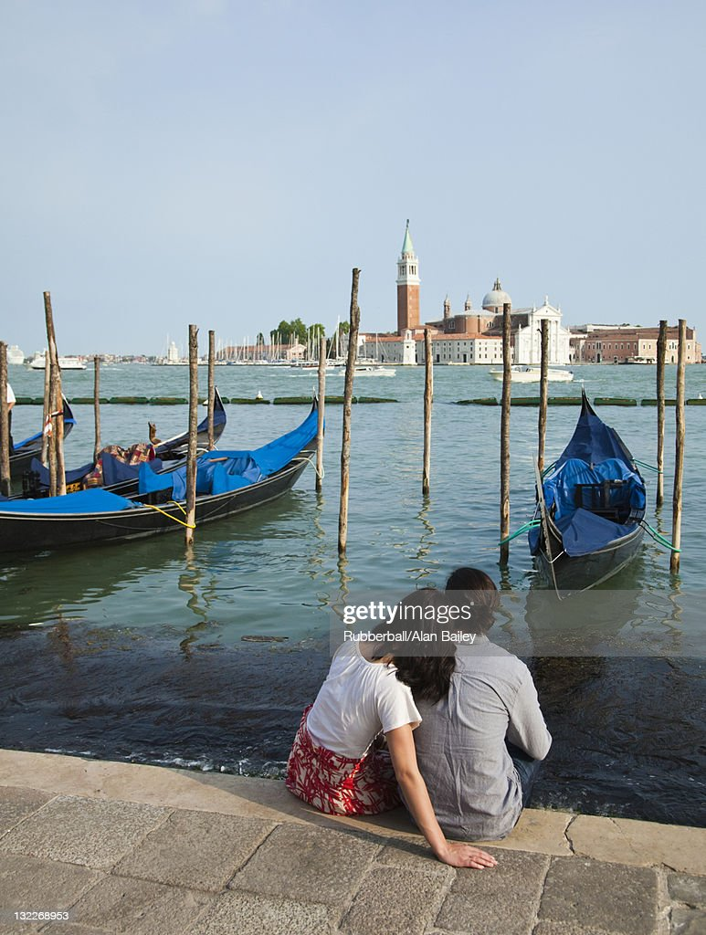 Italy, Venice, Rear view of couple sitting by lagoon : Stock Photo
