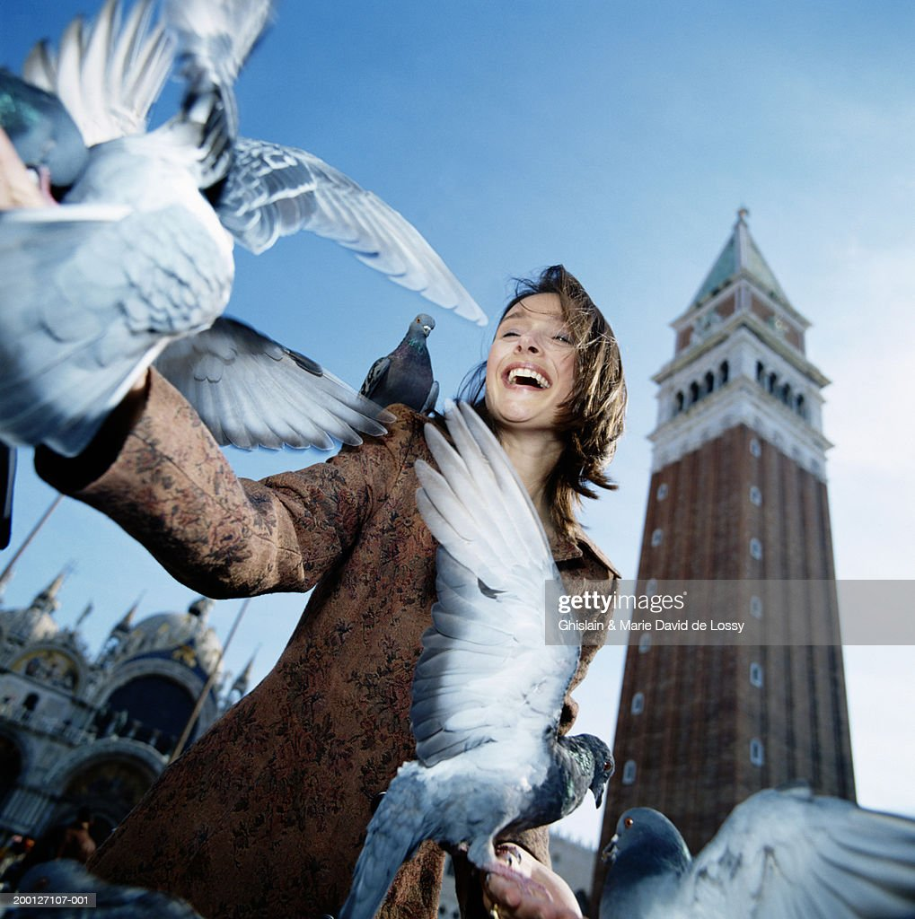 Italy, Venice, St Marks Square, woman feeding pigeons, low angle view : Stock Photo