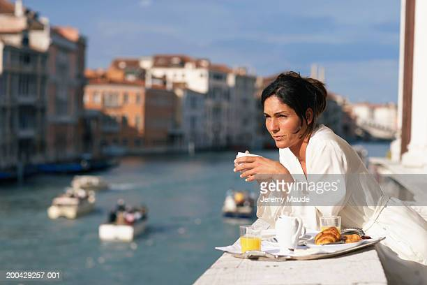 Italy, Venice, woman having breakfast on balcony on canal