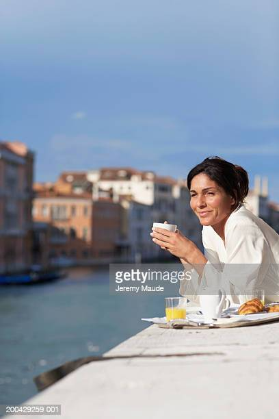 Italy, Venice, woman having breakfast on balcony, smiling