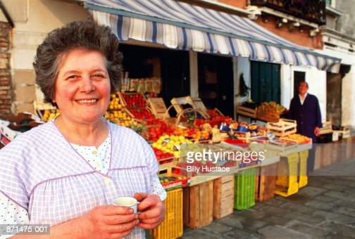 Italy, Venice, woman outside her fruit and vegetable store