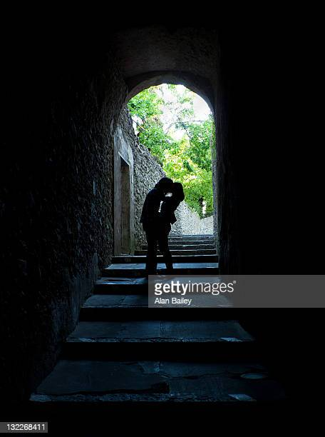 Italy, Venice, Young couple kissing in archway
