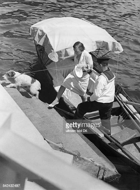 Young woman with dog getting out of a boat at the Lake Como 1933 Photographer Alfred Eisenstaedt Published by 'Die Dame' 28/1933 Vintage property of...
