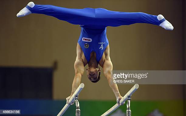 Italy's Andrea Cingolani performs on the parallel bars during the men's qualification at the Gymnastics World Championships as event mascots Nan Nan...