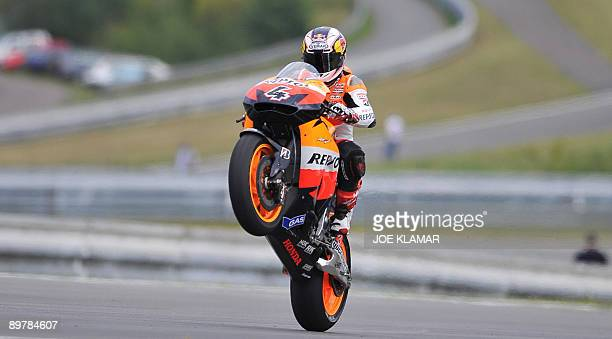 Italy's Andrea Dovizioso wheelies his motorbike as he finishes the first free practice session during the Czech Republic Moto Grand Prix in Brno on...