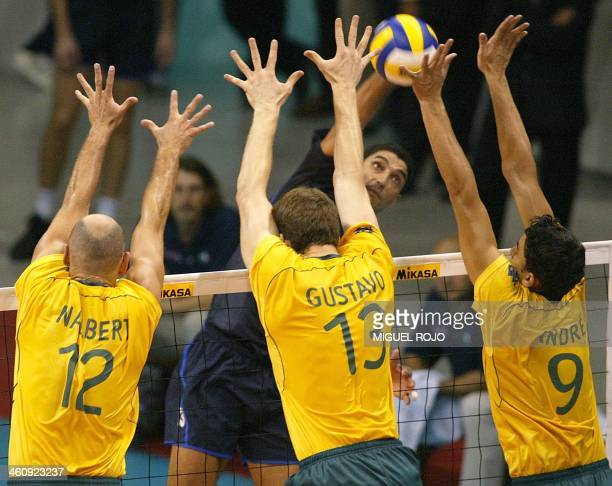 Italy's Andrea Giani spikes the ball against Brazil's Nalbert Gustavo and Andre during their 09 October Volleyball World Championship quarterfinal...