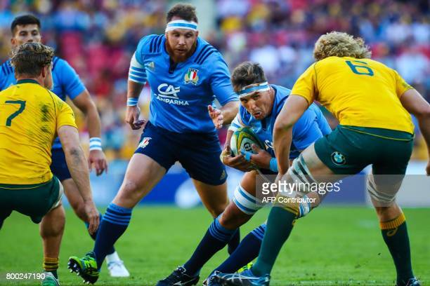 Italy's Andries Van Schalkwyk runs at Australian's Michael Hooper and Ned Hanigan during the international rugby match between Australia and Italy at...