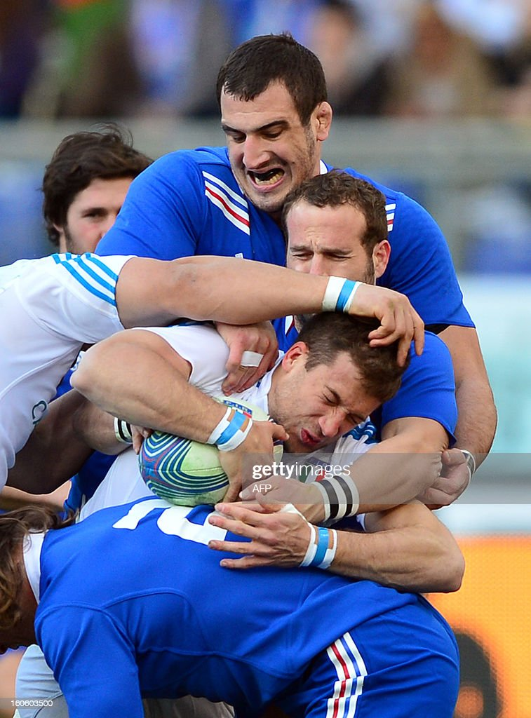 Italy's centre Tommaso Benvenuti is tackled by France's fly-half Frederic Michalak and France's lock Yoann Maestri (Top) during the Six Nations international rugby union match Italy vs France in Rome's Olimpic Stadium on February 3, 2013. Italy defeated France 23-18.