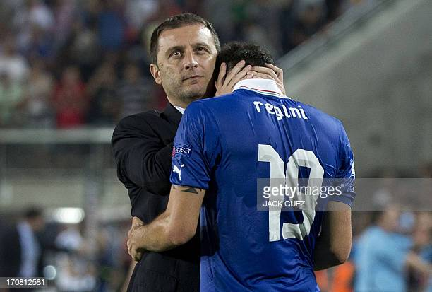 Italy's coach Devis Mangia comforts defender Vasco Regini after Spain beat Italy in their 2013 UEFA U21 Championship football match at Teddy Stadium...
