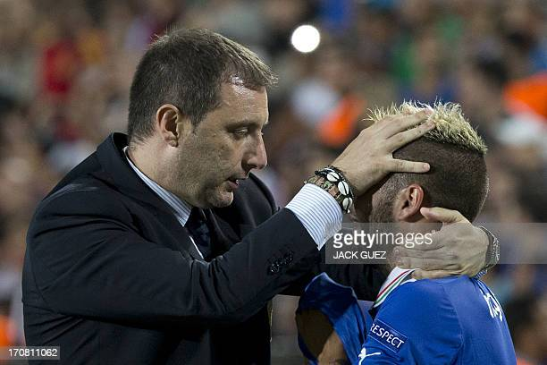 Italy's coach Devis Mangia comforts forward Lorenzo Insigne after Spain beat Italy in their 2013 UEFA U21 Championship football match at Teddy...