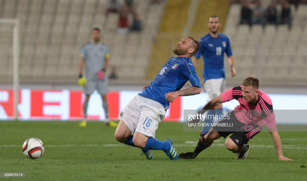 Italy's Daniele De Rossi (L) is tackled by Scotland's Matt Richie during the International friendly football match Italy vs Scotland at the National Stadium in Ta'Qali, Malta on May 29, 2016. / AFP / Matthew Mirabelli