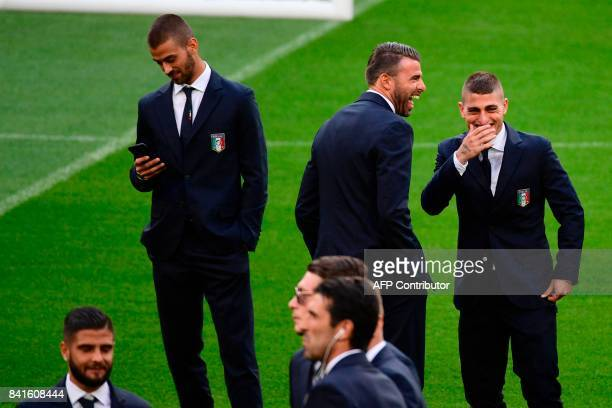 Italy's defender Andreas Barzagli and midfielder Marco Verratti share a laugh while walking around the Santiago Bernabeu stadium in Madrid on...