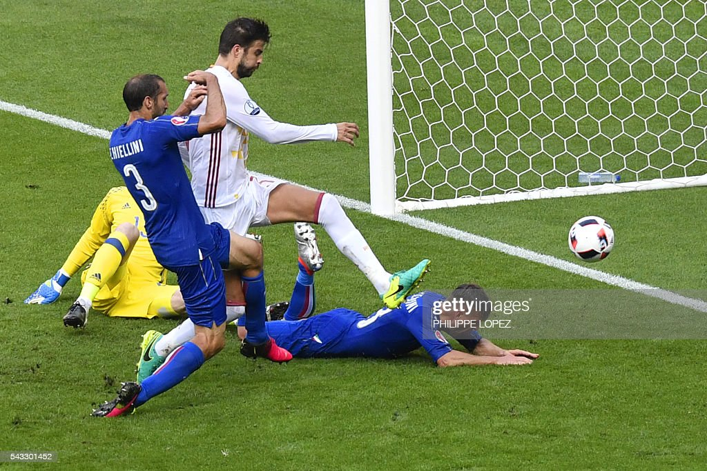 Italy's defender Giorgio Chiellini (L) shoots to score a goal beside Spain's defender Gerard Pique (2nd L) during Euro 2016 round of 16 football match between Italy and Spain at the Stade de France stadium in Saint-Denis, near Paris, on June 27, 2016. / AFP / PHILIPPE