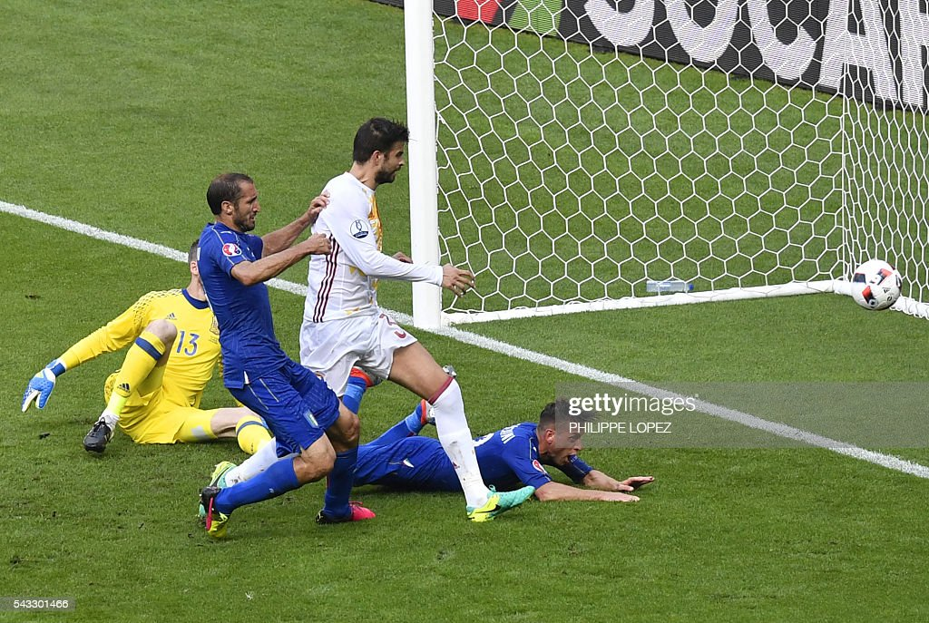 Italy's defender Giorgio Chiellini (2nd L) shoots to score a goal beside Spain's defender Gerard Pique (3rd L) during Euro 2016 round of 16 football match between Italy and Spain at the Stade de France stadium in Saint-Denis, near Paris, on June 27, 2016. / AFP / PHILIPPE