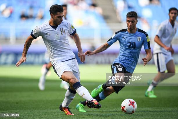 Italy's defender Giuseppe Pezzella passes the ball next to Uruguay's midfielder Rodrigo Bentancur during the U20 World Cup third place playoff...