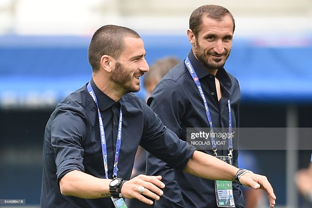 Italy's defender Leonardo Bonucci (L) jokes next to Giorgio Chiellini (R) as they walk around the pitch of the Bordeaux stadium on the eve of the match between Italy and Germany during the Euro 016, in Bordeaux, southwestern France, on July 1, 2016. / AFP / NICOLAS