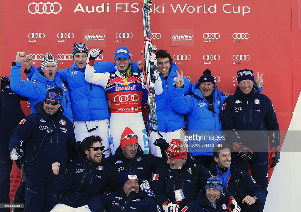 Italy's Dominik Paris (C) celebrates whit his teammates and staff members on the podium after winning the FIS World Cup men's downhill race on January 26, 2013 in Kitzbuehel, Austrian Alps. AFP PHOTO / ALEXANDER KLEIN