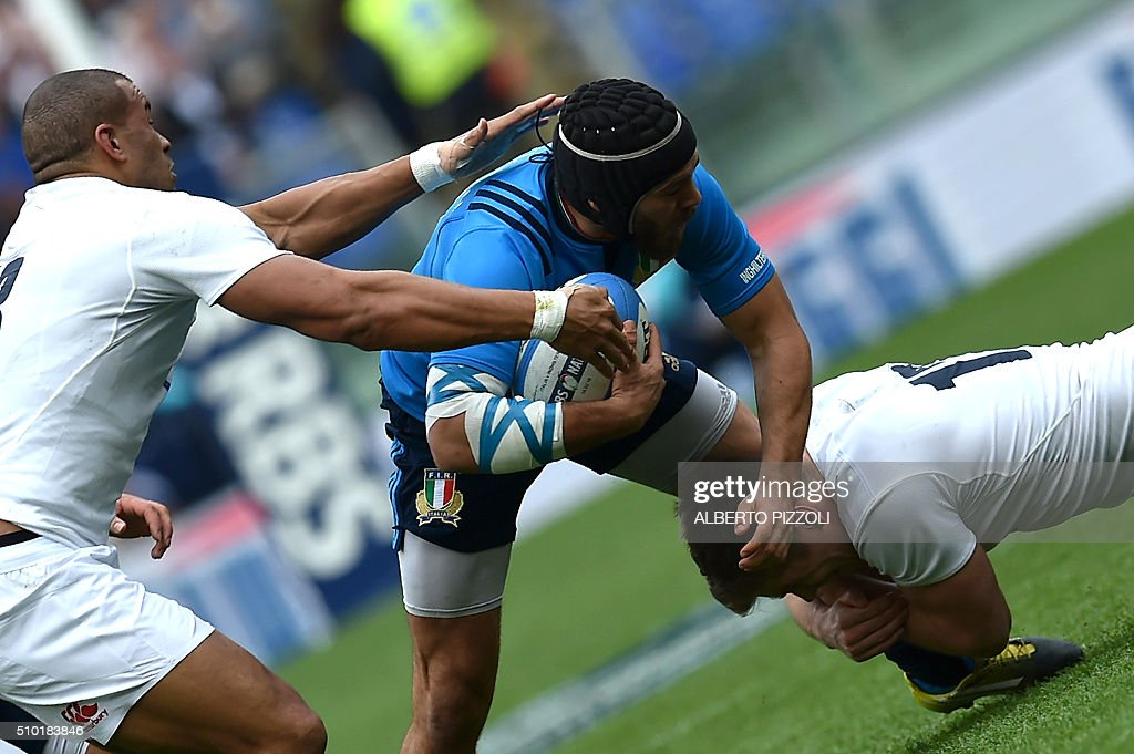 Italy's Edoardo Gori (C) is takled by England's centre Jonathan Joseph (L) and England's wing Mike Brown during the Six Nations international rugby union match between Italy and England on February 14, 2016 at Olympic stadium in Rome. / AFP / ALBERTO PIZZOLI