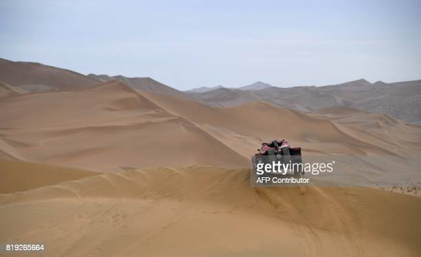 Italy's Eugenio Amos and his codriver Sebastien Delaunay of France ride over sand dunes as they compete during the Stage 12 of the Silk Way 2017...