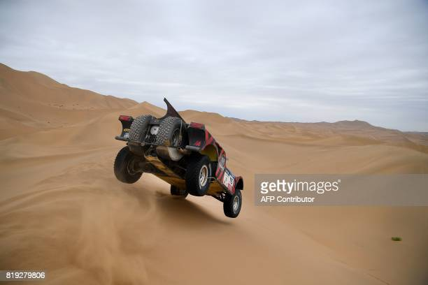 Italy's Eugenio Amos and his codriver Sebastien Delaunay of France ride over sand dunes while competing during the Stage 12 of the Silk Way 2017...