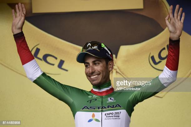 Italy's Fabio Aru arrives on the podium to celebrate his overall leader yellow jersey at the end of the 101 km thirteenth stage of the 104th edition...