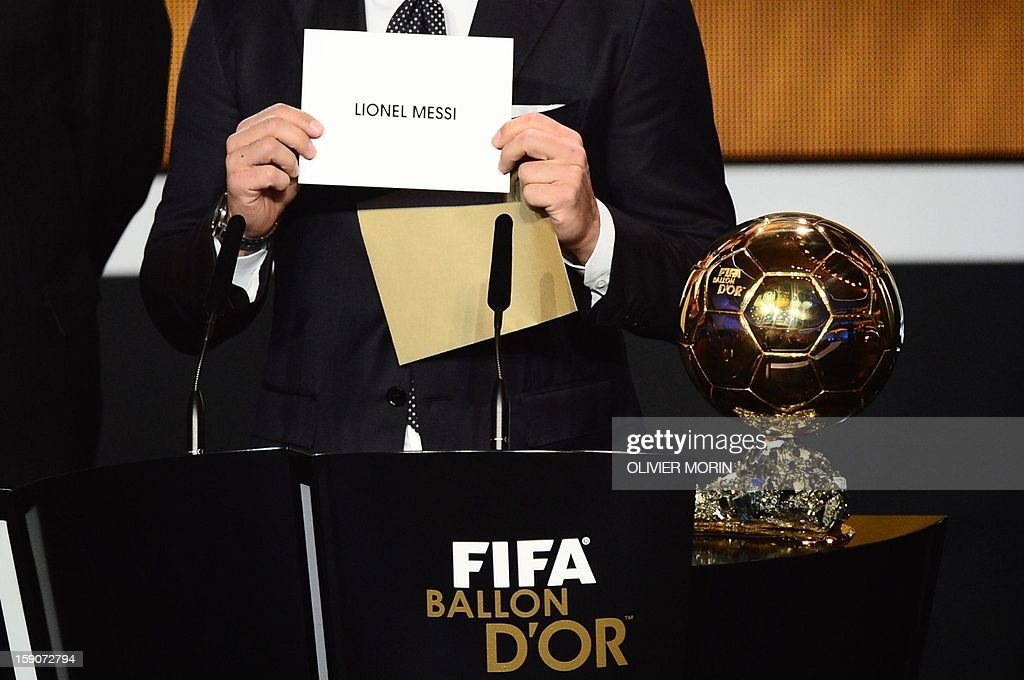 Italy's Fabio Cannavaro shows the envelope with the name of the winner, Barcelona's Argentinian forward Lionel Messi of the FIFA Ballon d'Or award from FIFA President Joseph Blatter (R) during the FIFA Ballon d'Or awards ceremony at the Kongresshaus in Zurich on January 7, 2013. AFP PHOTO / OLIVIER MORIN