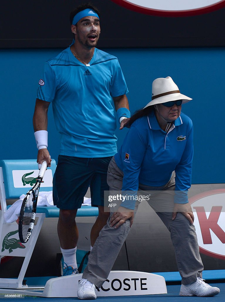 Italy's Fabio Fognini (L) leans on a lineswoman as he prepares to play a shot during his men's singles match against Serbia's Novak Djokovic on day seven of the 2014 Australian Open tennis tournament in Melbourne on January 19, 2014. IMAGE
