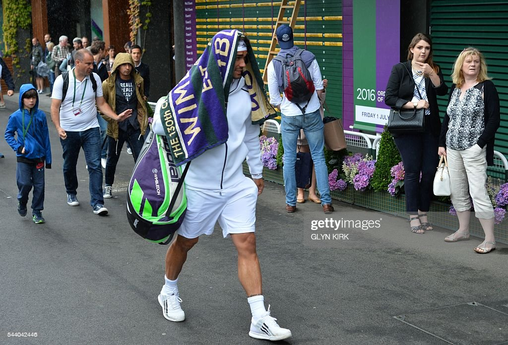 Italy's Fabio Fognini leaves court 16 after rain halts play on the fifth day of the 2016 Wimbledon Championships at The All England Lawn Tennis Club in Wimbledon, southwest London, on July 1, 2016. / AFP / GLYN