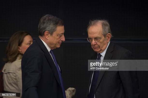 Italy's Finance Minister Pietro Carlo Padoan and President of the European Central Bank Mario Draghi chat during an informal meeting of the Eurozone...