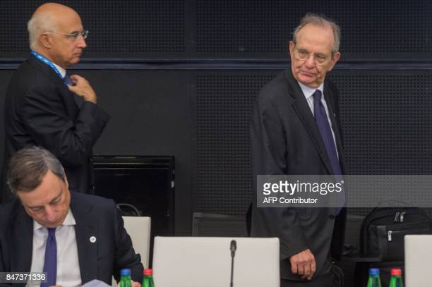 Italy's Finance Minister Pietro Carlo Padoan passes by President of the European Central Bank Mario Draghi during an informal meeting of the Eurozone...