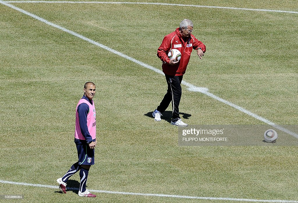 Italy's football team coach Marcello Lippi (R) looks at his watch as captain Fabio Cannavaro walks during a training camp in Sestriere on May 24, 2010 ahead of the 2010 FIFA World Cup in South Africa. AFP PHOTO / Filippo MONTEFORTE