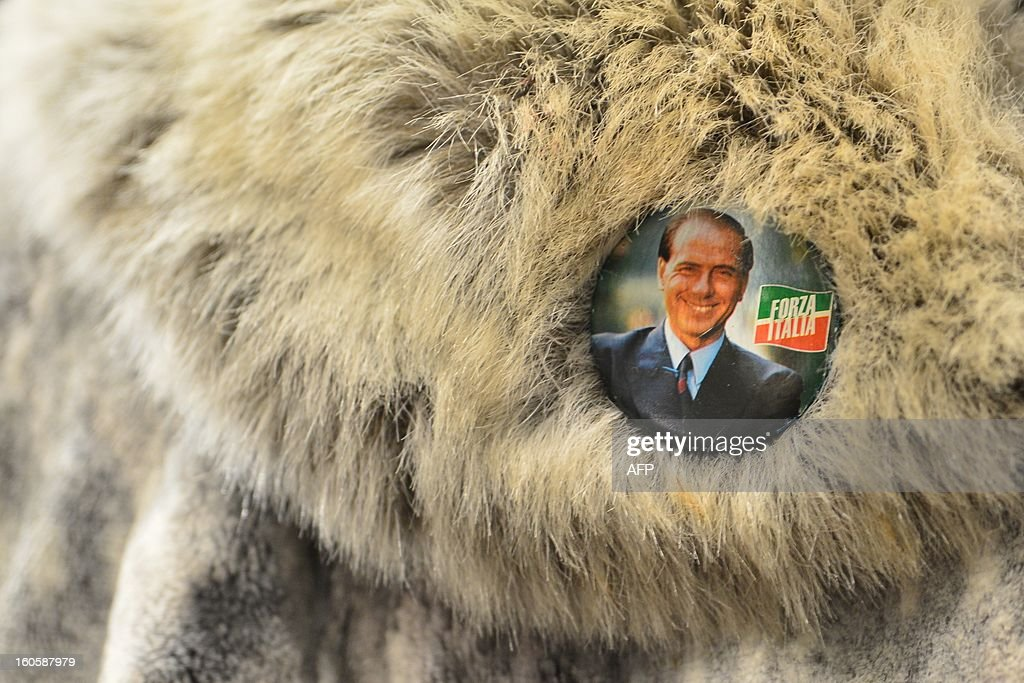 Italy's former prime minister Silvio Berlusconi is seen on a badge of a supporter during a rally of his party the Popoplo della liberta (PDL) on February 3, 2013 in Milan.