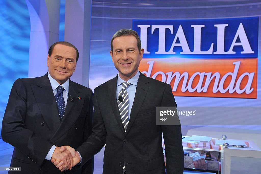 Italy's former Prime Minister Silvio Berlusconi (L) shakes hands with presenter Alberto Bila on the set of 'Italia Domanda' (Italy's question) of the Canale 5 television channel on January 18, 2013 in Rome.