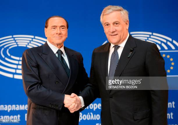 Italy's former Prime Minister Silvio Berlusconi shakes hands with European Parliament President Antonio Tajani at the European Parliament in...