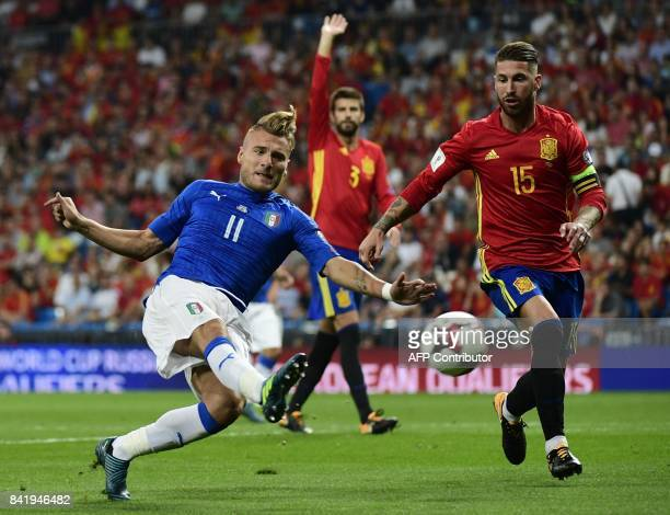 Italy's forward Ciro Immobile shoots the ball beside Spain's defender Sergio Ramos as Spain's defender Gerard Pique raises his hand during the World...