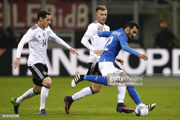 Italy's forward Giuseppe Zappacosta fights for the ball with Germany's midfielder Sebastian Rudy and Germany's midfielder Yannick Gerhardt during the...
