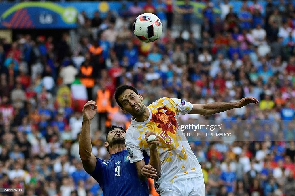 Italy's forward Pelle and Spain's midfielder Sergio Busquets vie for the ball during the Euro 2016 round of 16 football match between Italy and Spain at the Stade de France stadium in Saint-Denis, near Paris, on June 27, 2016. MARCOU