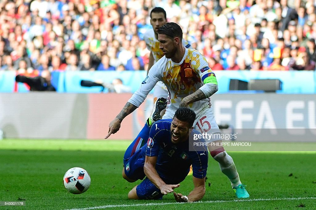 Italy's forward Pelle (bottom) is challenged by Spain's defender Sergio Ramos during the Euro 2016 round of 16 football match between Italy and Spain at the Stade de France stadium in Saint-Denis, near Paris, on June 27, 2016. / AFP / PIERRE