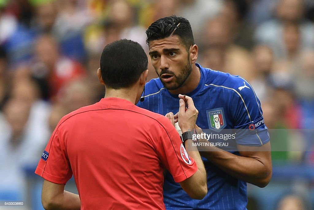 Italy's forward Pelle reacts as he receives a yellow card from Turkish referee Cuneyt Cakir during Euro 2016 round of 16 football match between Italy and Spain at the Stade de France stadium in Saint-Denis, near Paris, on June 27, 2016. / AFP / MARTIN