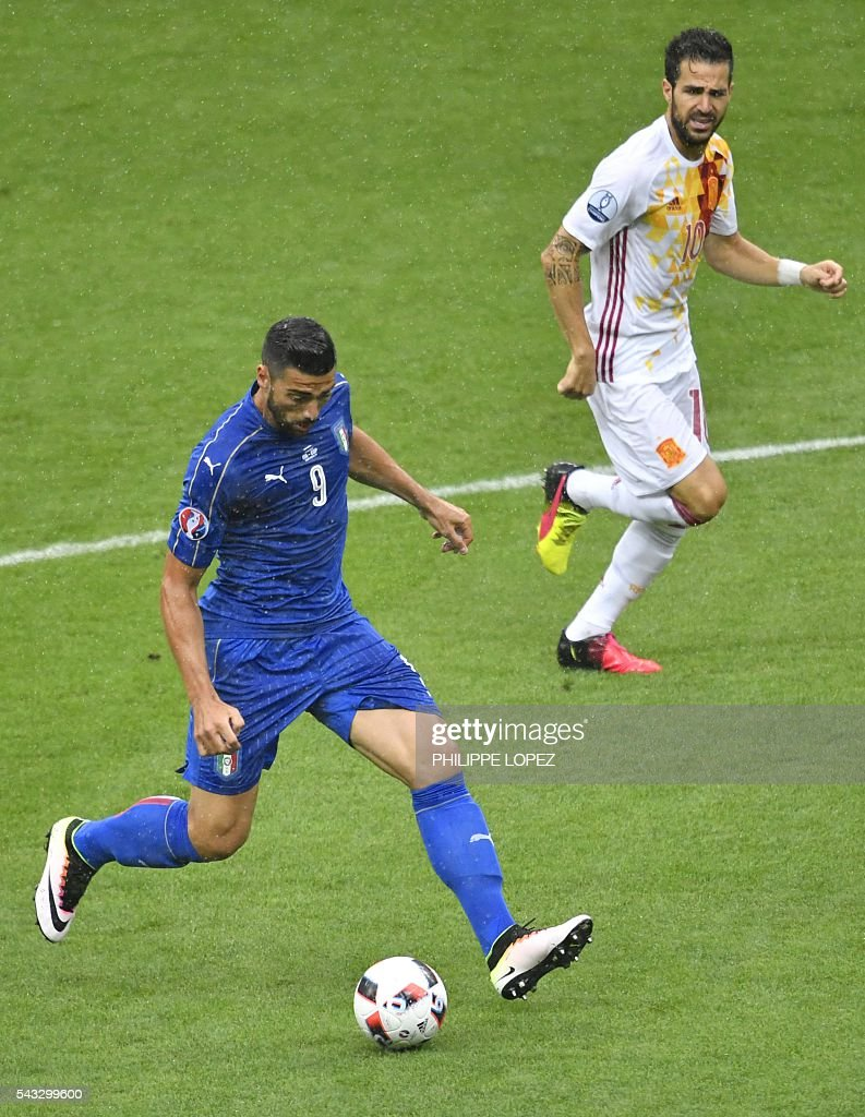 Italy's forward Pelle (L) rus with the ball beside Spain's midfielder Cesc Fabregas during Euro 2016 round of 16 football match between Italy and Spain at the Stade de France stadium in Saint-Denis, near Paris, on June 27, 2016. / AFP / PHILIPPE