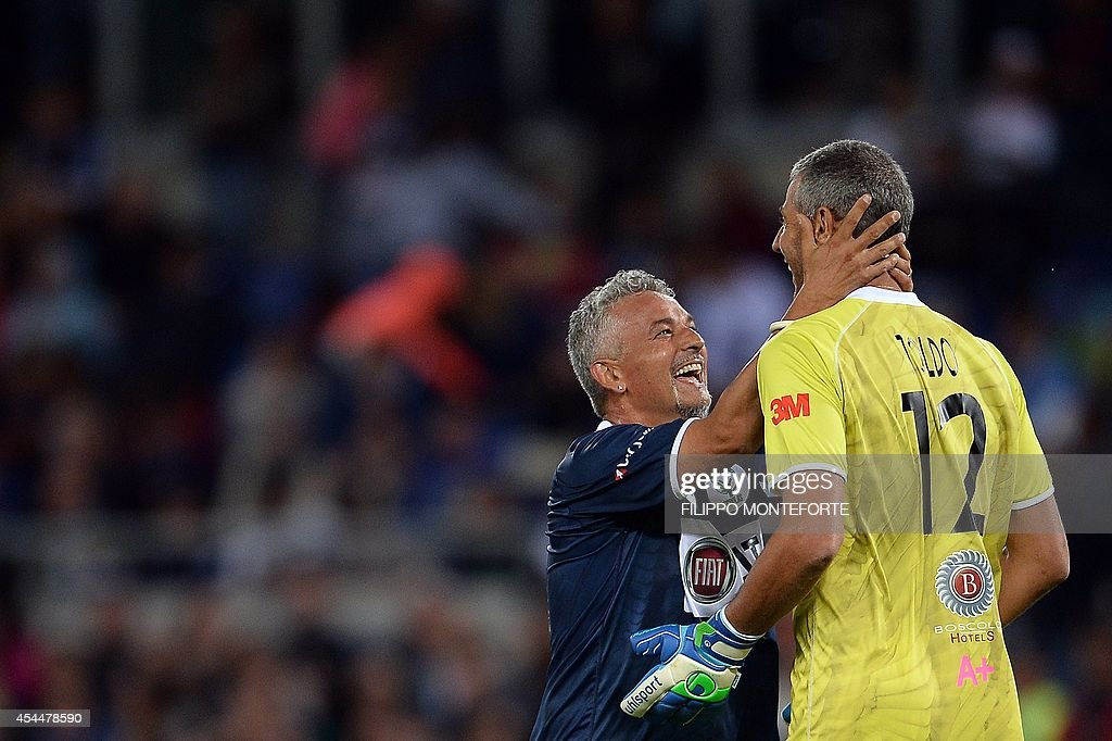 Italy's forward Roberto Baggio (L) hugs goalkeeper Paolo Toldo during the inter religious 'match for peace' football game in Rome's Olympic Stadium on September 1, 2014. AFP PHOTO/Filippo MONTEFORTE