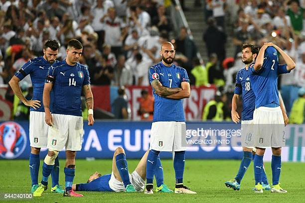 TOPSHOT Italy's forward Simone Zaza reacts along with teammates after loosing the penalty shootout to Germany in the Euro 2016 quarterfinal football...