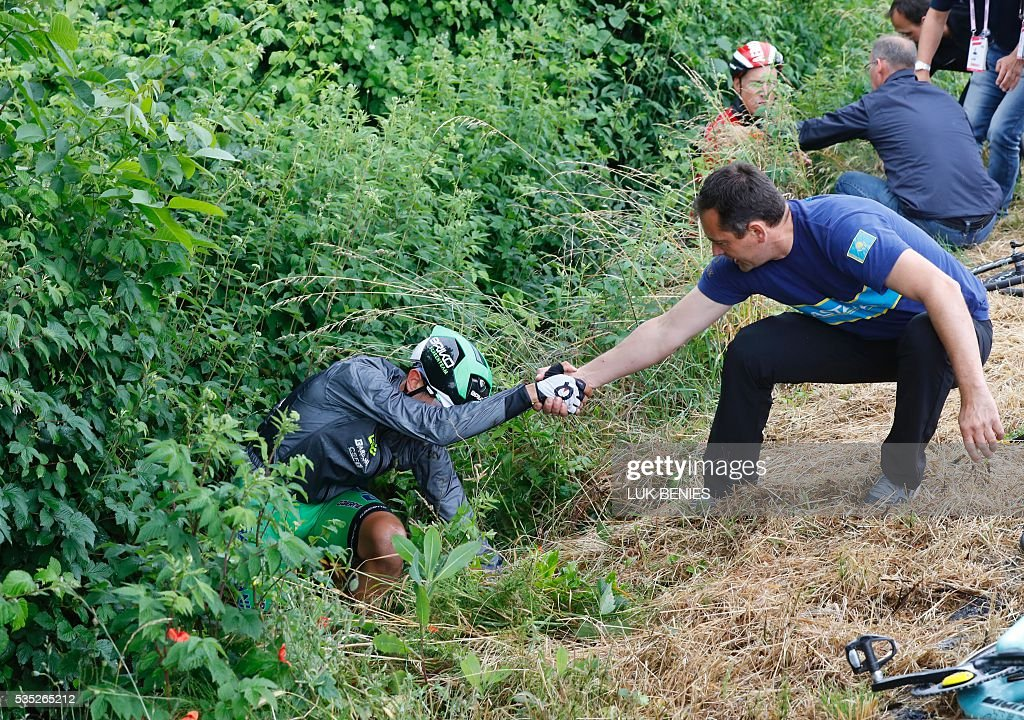 Italy's Francesco Manuel Bongiorno receives help after a fall during the 21th and last stage of the 99th Giro d'Italia, Tour of Italy, from Cuneo to Turin on May 29, 2016. / AFP / Luk BENIES