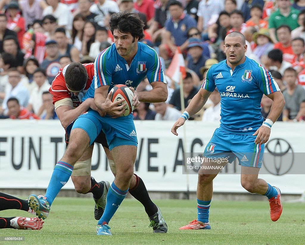 Italy's full-back Luke Mclean (C) is tackled by Japan's locks Luke Thompson (L) during a friendly rugby union match in Tokyo on June 21, 2014. Japan defeated Italy 26-23. AFP PHOTO/Toru YAMANAKA