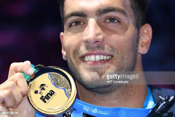 Italy's Gabriele Detti celebrates poses with his gold medal during the podium ceremony for the men's 800m freestyle final during the swimming...